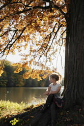 Little girl sitting under autumn tree looking at the river - EYAF00600