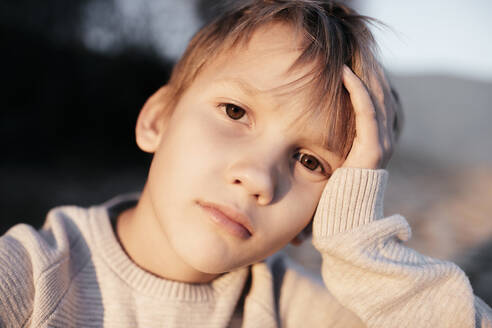 Portrait of pensive boy with head in his hand - EYAF00603