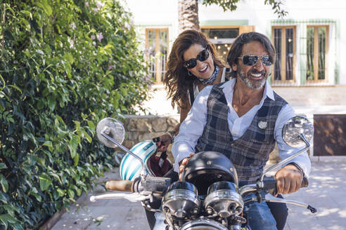 Portait of happy mature couple on a vintage motorbike - DLTSF00254
