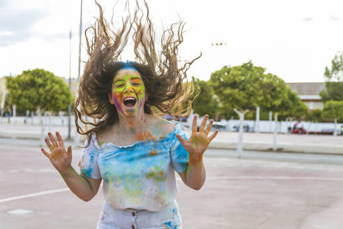 Teenage girl jumps and screams for joy, playing with colored powders a - CAVF65180