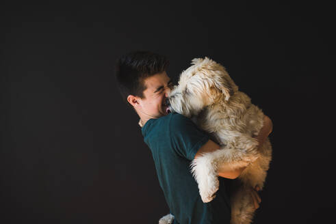 Teenage boy holding a fluffy dog that his licking him on the face. - CAVF65246