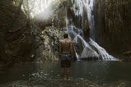 Man standing near waterfall - CAVF65279