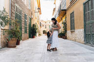 Alcúdia, Mallorca, Spain. Two year old girl hugging her pregnant mother on the street - GEMF03209