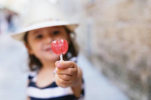 Little girl's hand holding heart-shaped lollipop, close-up - GEMF03212