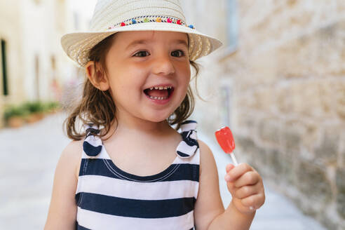Portrait of happy little girl with red lollipop in summer - GEMF03215