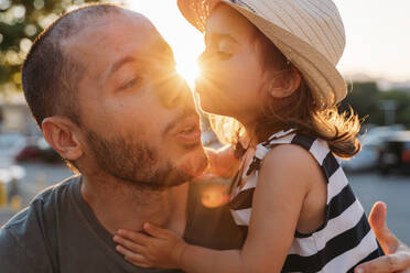Little girl kissing her father at sunset - GEMF03224