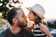 Little girl kissing her father at sunset - GEMF03227