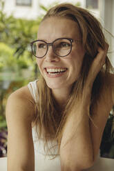 Portrait of happy young woman with glasses looking sideways - MFF04879