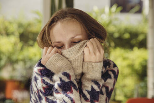 Portrait of young woman with closed eyes sinking in her woolen sweater - MFF04882