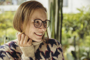 Portrait of smiling young woman with glasses wearing fluffy sweater looking sideways - MFF04885