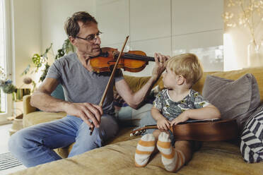 Toddler watching his father playing violin - MFF04891