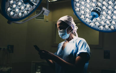 Nurse using a mobile phone in operating room - DAMF00190