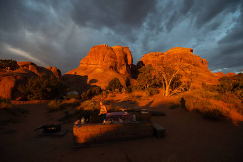 A woman at sunrise in Devil's Garden Campground, Arches National Park - CAVF65464