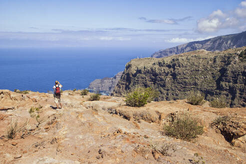 Hiker at the coast enjoying the view, Agulo, La Gomera, Canary Islands, Spain - MAMF00882