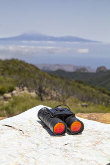 Spain, Canary Islands, La Gomera, Binoculars and map lying at summit of Garajonay with Teide volcano looming in distant background - MAMF00894