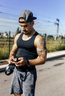 Sporty young man with smartphone and headphones standing on a road - MGOF04127