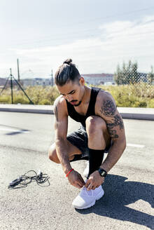 Sporty young man tying shoes before training on a road - MGOF04136