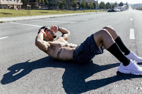 Young man doing sit-ups on a road - MGOF04142