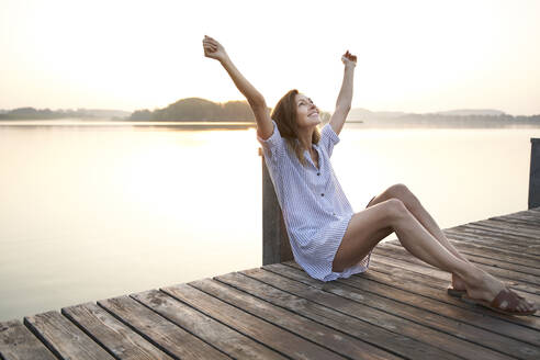 Happy mature woman sitting on jetty at a lake at sunrise - PNEF02179