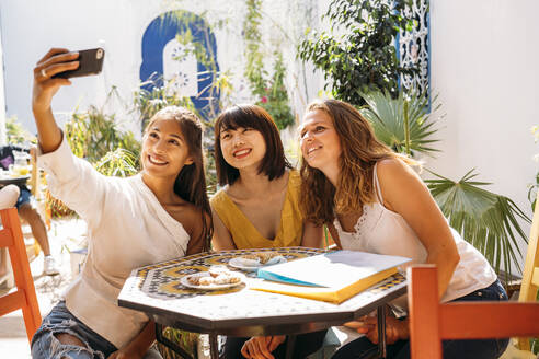 Three happy female friends meeting in a cafe taking a selfie - MPPF00124