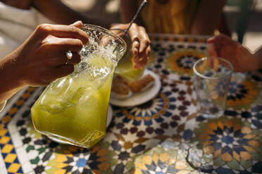 Woman serving lemonade to her friends in a Moroccan cafe - MPPF00127