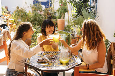 Three happy female friends meeting in a cafe clinking lemonade glasses - MPPF00130