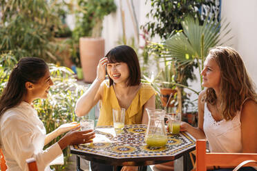 Three happy female friends meeting in a cafe drinking lemonade - MPPF00133