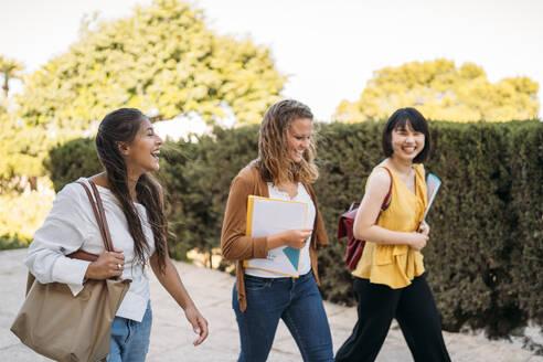 Three happy female friends walking around in a park - MPPF00145