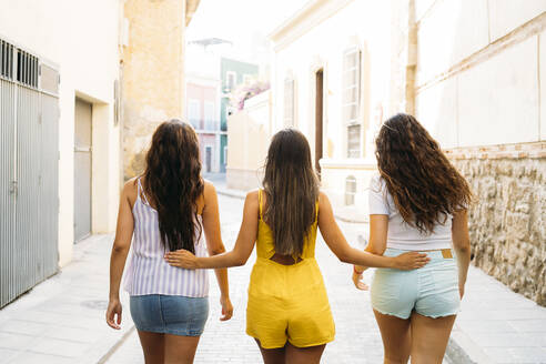Rear view of three female friends walking in an alley - MPPF00154