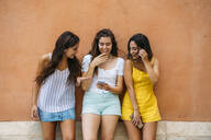Three happy female friends standing at a wall sharing smartphone - MPPF00163