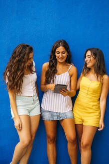 Three happy female friends standing at a blue wall sharing tablet - MPPF00178