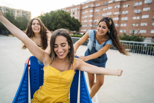 Three playful female friends with shopping cart in the city - MPPF00190