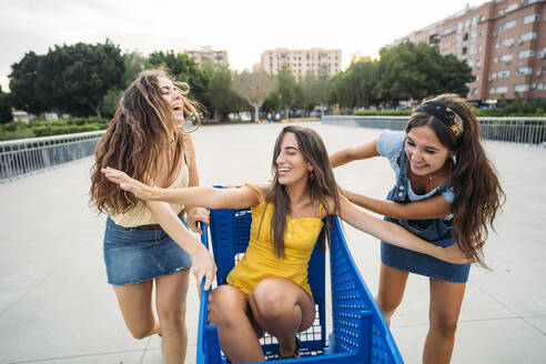Three playful female friends with shopping cart in the city - MPPF00193