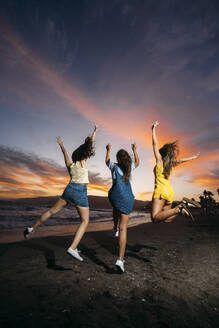 Rear view of three carefree female friends jumping on the beach at sunset - MPPF00202
