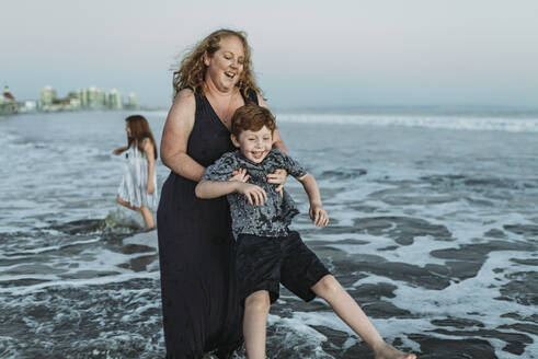 Young mother playing with young redhead son in ocean at dusk - CAVF65530