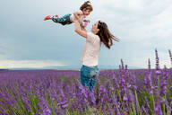 Woman throwing little girl in the air among lavender fields in summer - CAVF65569