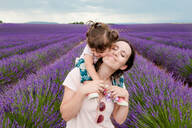 Mother and daughter walking among lavender fields in the summer - CAVF65572