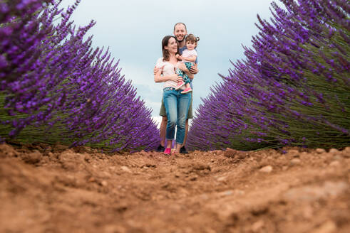 Happy family walking among lavender fields in the summer - CAVF65575