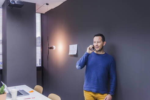 Side view of businessman talking on smart phone while standing against office wall - CAVF65594