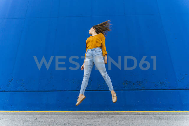 Young woman jumping in front of a blue wall - AFVF04065 - VITTA GALLERY/Westend61