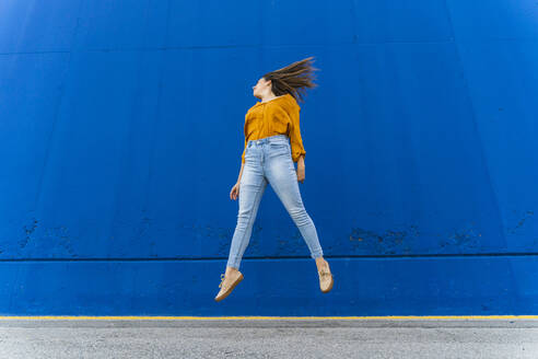Young woman jumping in front of a blue wall - AFVF04065