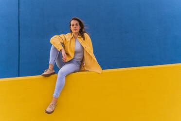 Young woman sitting on an yellow wall - AFVF04071