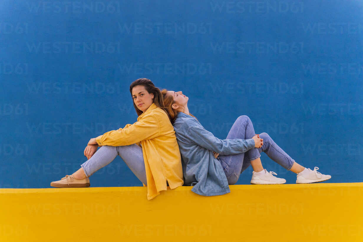 Young beautiful carefree women sitting on an orange wall - AFVF04074 - VITTA GALLERY/Westend61