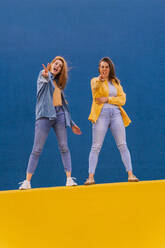 Young women standing on an orange wall and showing peace sign - AFVF04077