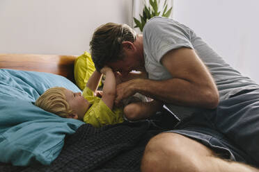 Father cuddling and tickling son on bed - MFF04931