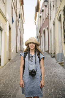 Portrait of woman with camera in an alley in the old town of Coimbra, Portugal - AHSF00932