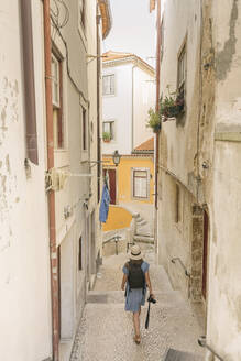 Tourist walking in an alley in the old town of Coimbra, Portugal - AHSF00935