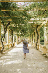 Rear view woman walking in a beautiful passage full of plants in the park, Aveiro, Portugal - AHSF00938
