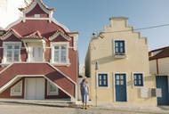 Woman standing in front of houses, Costa Nova, Portugal - AHSF00947