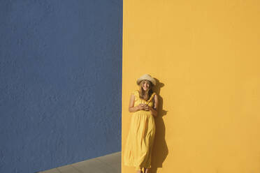 Woman in a yellow dress using smartphone in front of yellow and blue walls - AHSF00962